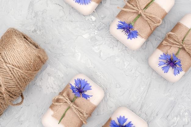 Handgemaakte natuurzeepset versierd met kraftpapier, gesel en blauwe bloemen.