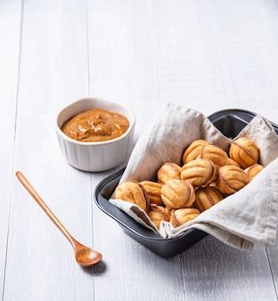 Handgemaakte noten gebakken met gekookte melk en karamel in een ovenschaal op een witte tafel. kopieer ruimte