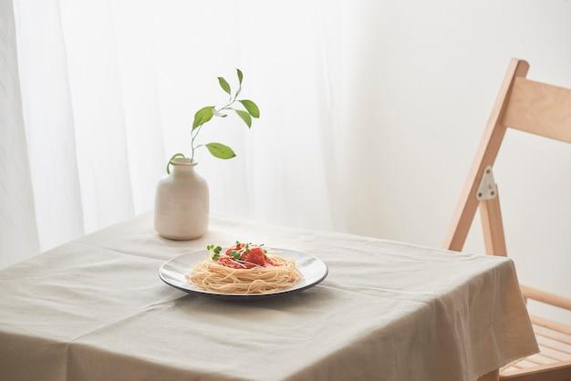 Handgemaakte pasta met ragoutsaus op bord op vintage witte tafel met vergiet en bloemen