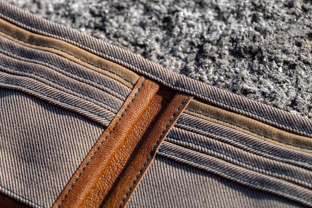 Handgemaakte portemonnee van bruin leer en geruit textiel op steen