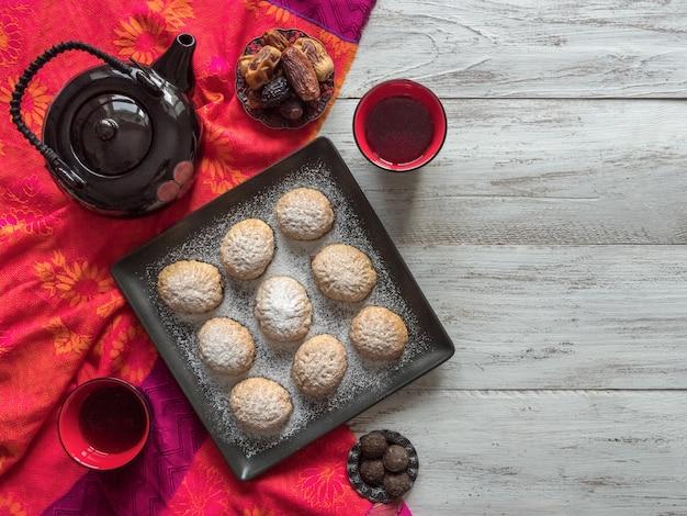Handgemaakte ramadan-snoepjes worden geserveerd met thee op de achtergrond. egyptische koekjes