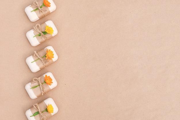 Handgemaakte rand van natuurlijke zeep, versierd met kraftpapier, plaag en oranje calendula-bloemen. biologische cosmetica