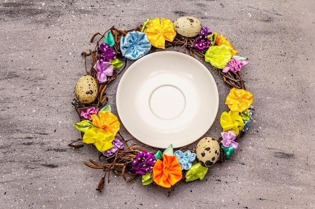 Handgemaakte rieten krans van pasen met kwarteleitjes en handgemaakte bloemen