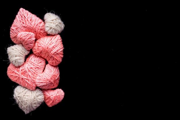 Handgemaakte roze en witte wol garen hart geïsoleerd op zwart