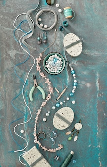 Handgemaakte sieraden maken voor vrienden als kerstcadeaus. plat lag op donkere cyaan muur.