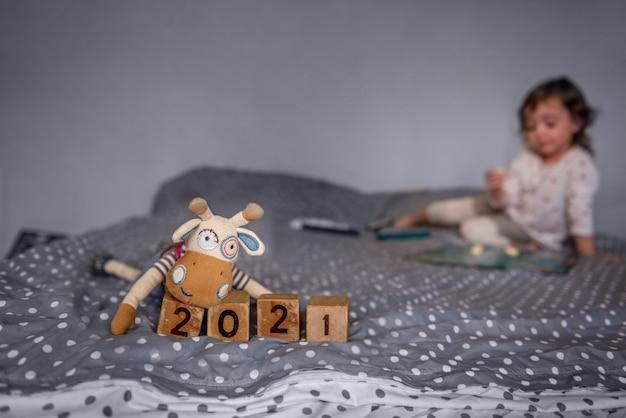 Handgemaakte speelgoedstier op houten kubussen met de cijfers 2021