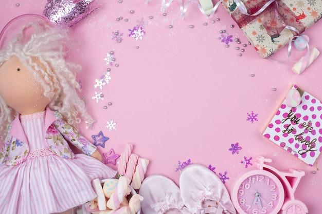 Handgemaakte textielpop, marshmallow-pictogrammen en satijnen slippers voor een meisje op een roze. klok in de vorm van een fiets