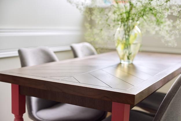 Handgemaakte timmerlieden houten eiken tafel in het interieur van de woonkamer, op tafelvaas met bloemen, stoelen