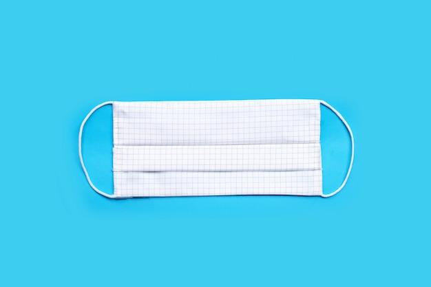 Handgemaakte witte doek masker op blauwe achtergrond. bovenaanzicht