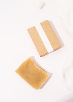 Handgemaakte zeep en ambachtelijke doos voor mock-up ontwerp op witte achtergrond, bovenaanzicht plat lag flat