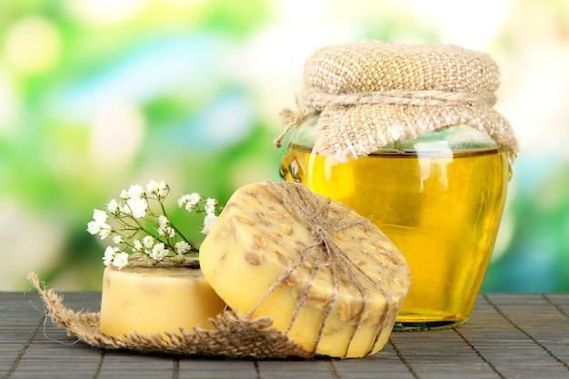 Handgemaakte zeep en ingrediënten voor het maken van zeep op bamboe mat, op groen