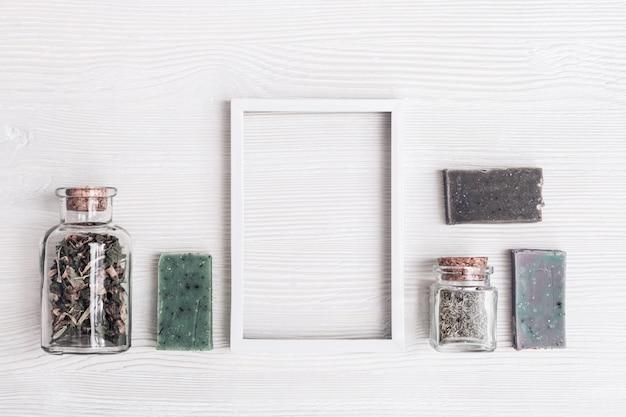 Handgemaakte zeep met natuurlijke organische ingrediënten met aromatische kruiden voor lichaamsverzorging en wellness. ontspanning en zen-achtig concept. plat lag spa samenstelling op witte houten tafel met kopie ruimte.