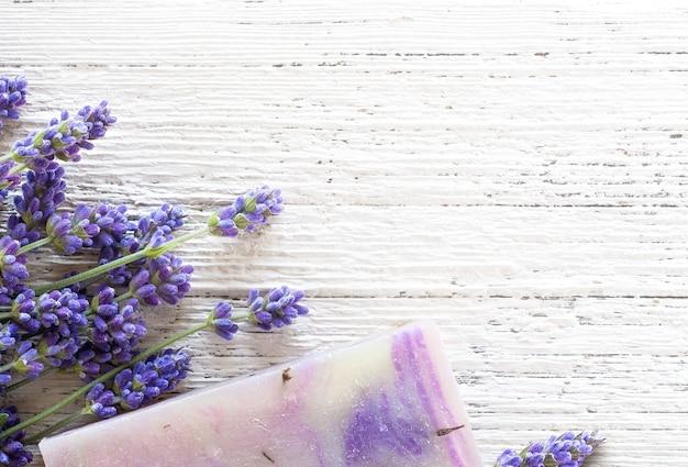 Handgemaakte zeepreep met lavendelbloemen op witte houten achtergrond met kopieerruimte