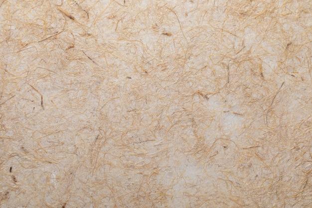 Handgeschept papier textuur met plantaardige vezels zoals stro. in delicate tonen, geel, sinaasappels, bruin en vanille.