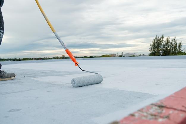 Handgeschilderde grijze vloer met verfrollers voor waterdicht wapeningsnet