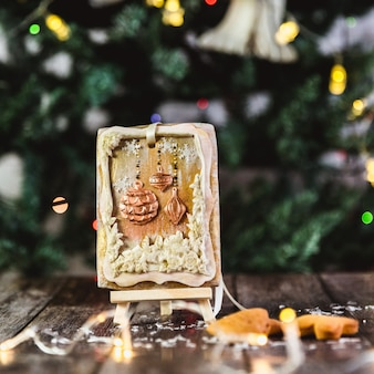 Handgeschilderde kerstpeperkoek op een houten standaard met abstracte bokeh. detailopname.