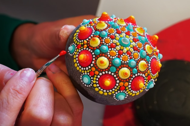 Handgeschilderde mandala op steen met penseel