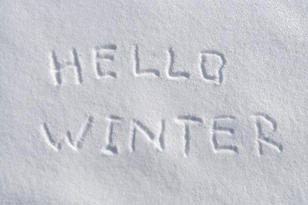 Handgeschreven hallo winter op de verse sneeuwachtergrond