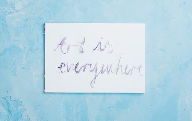 Handgeschreven 'kunst is overal' tekst op wit papier over ruwe textuur