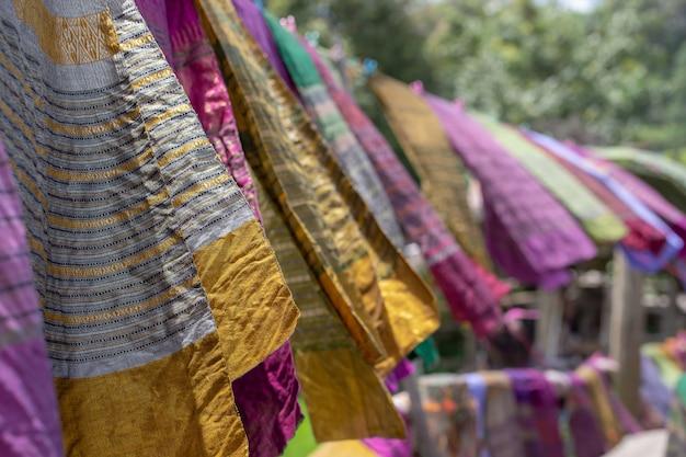 Handgeweven kleding hangt aan houten looppaden in het rijstveld van sila laeng