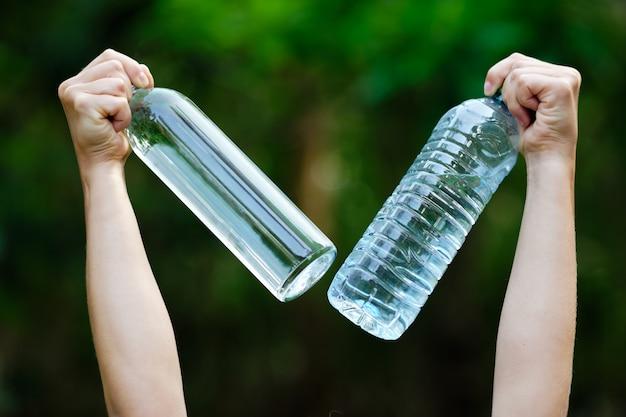 Handgreep water leeg glas en plastic fles