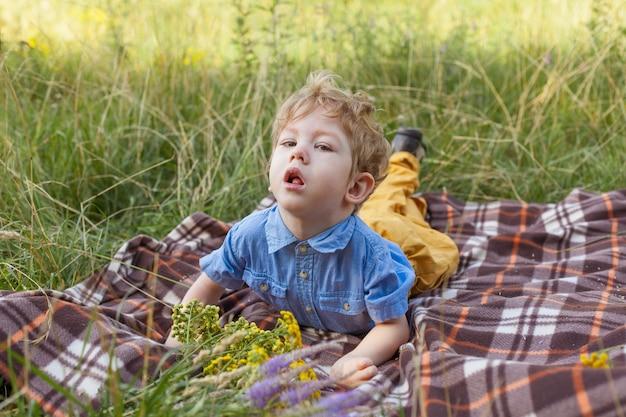 Handicap bij een jongen, kinderen met een handicap, een kind dat op een kleed in het park ligt, verlamming bij een kind.