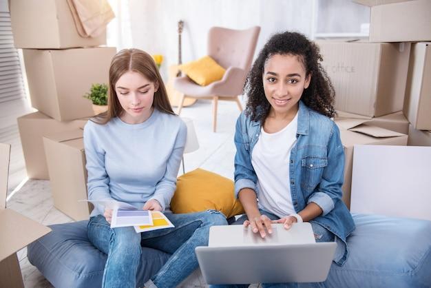 Handig winkelen. charmante vrouwelijke studenten zittend op de vloer tussen dozen met hun bezittingen en online verf kopen voor nieuwe flat