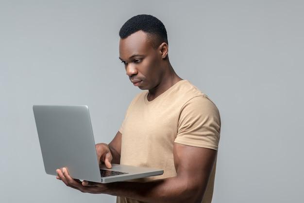 Handige gadget. jonge volwassen ernstige donkere gevilde man kijken naar werkende laptop bedrijf in handen staan in de studio