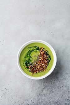 Handige smoothies van spinazie met boekweitvlokken in keramische kommen op grijs betonnen tafelblad. selectieve aandacht. bovenaanzicht.