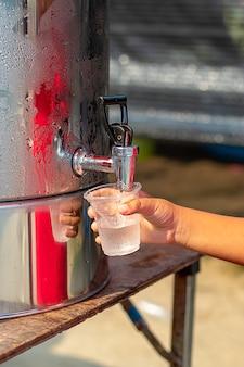 Handjongen die het glas met water van de waterkoeler houdt.