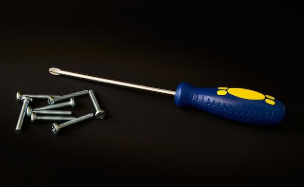 Handkers schroevendraaier met het blauwe handvat en schroeven op donkere ruimte, armatuur, gereedschap