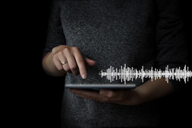 Handklikken op de tablet om naar muziek te luisteren, naar muziek te luisteren op mobiele apparaten, conceptmuziek