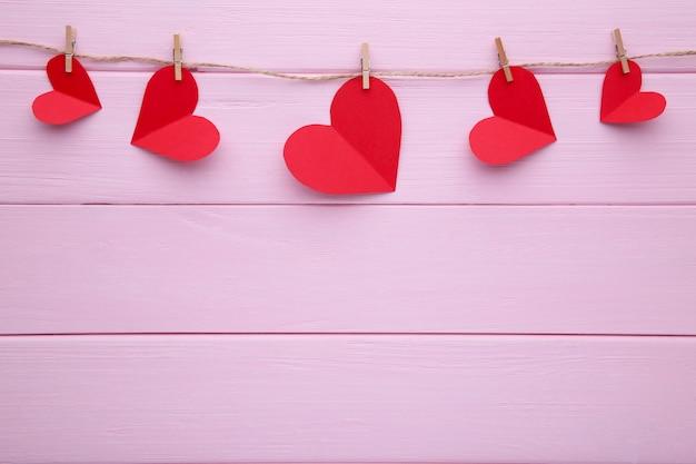 Handmaded harten op een touw op roze achtergrond.