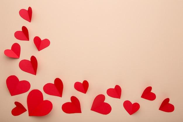 Handmaded rode harten op beige achtergrond.