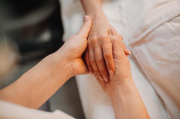 Handmassageprocedure uitgevoerd door een zorgvuldige kaukasische masseur in de spa-salon