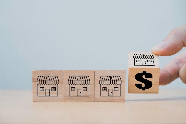 Handmatig omdraaien van houten kubusblok voor verandering van franchisewinkel naar dollarteken, franchise-ontwikkelingsconcept uitbreiden.