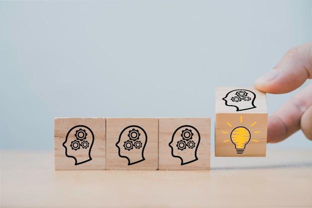 Handmatig omkeerbaar houten kubusblok dat het schermgezicht met vraagteken naar gloeilamp, creatief idee en innovatieconcept afdrukt.