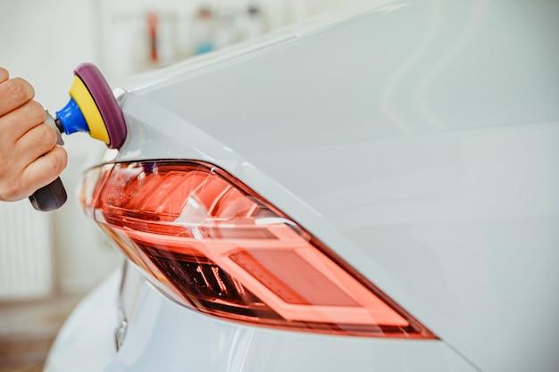 Handmatig polijsten van de carrosserie van luxe auto's met toepassing van keramische beschermingsmiddelen. kopieer ruimte
