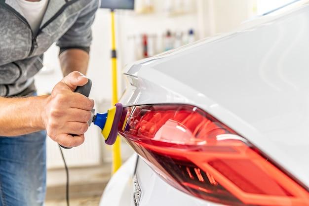 Handmatig polijsten van de koplamp van luxe auto's met toepassing van beschermende uitrusting