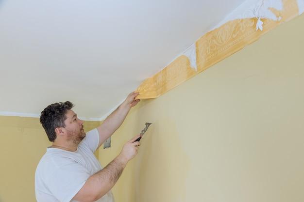 Handmatig werk met schraper die hand oud behang op de muur schrapt met voorbereiding voor het schilderen van een kamer