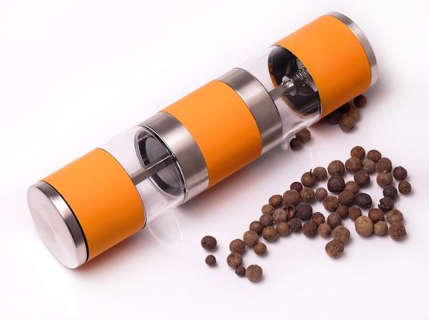Handmatige pepperbox en gemorste peper op het witte oppervlak
