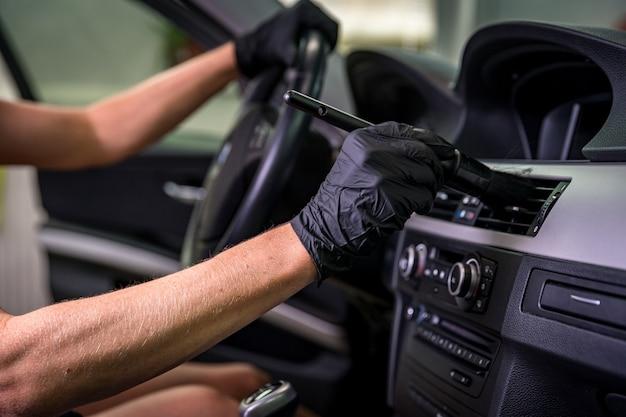 Handmatige reiniging van het auto-interieur met behulp van borstelen.