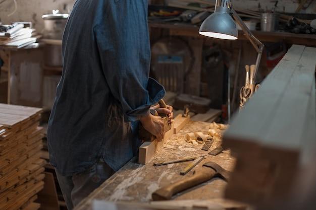 Handmatige vrouwenarbeid. vrouw werkt in een houtwerkplaats. close-up van vrouwelijke handen met een hulpmiddel
