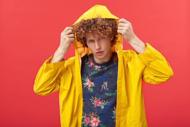 Handosme jonge hipster die de kap van zijn gele modieuze anorak aanpast voordat hij uitgaat