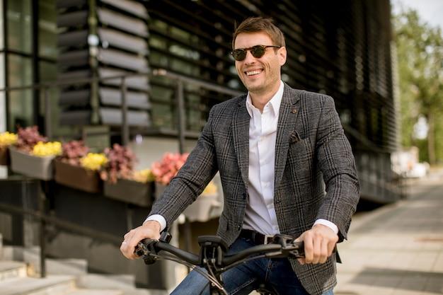 Handosme jonge zakenman op de ebike op straat