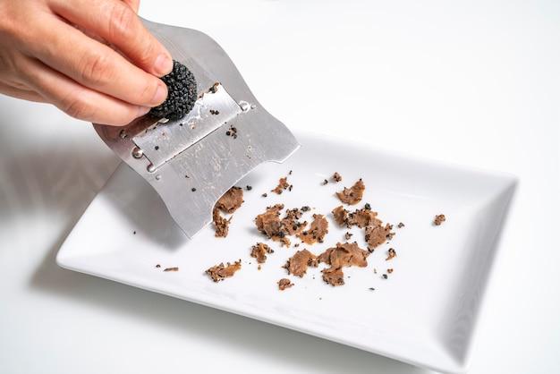 Handplak zwarte truffel met truffelsnijder op witte achtergrond delicatesse truffelpaddestoel