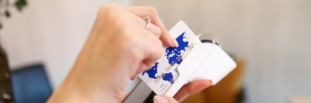 Hands houdt draagbare terminal voor kaartbetaling. betalingsdienstaanbieders. mogelijkheid om creditcards internet te accepteren. kaarthouder betaalt voor aankopen op sites, webwinkels en services tijdens quarantaine
