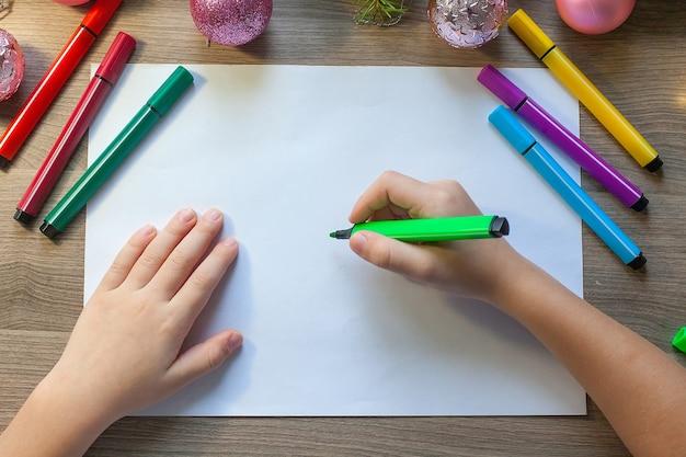Hands tekent een kerstboom met een gekleurde viltstift, zittend aan de tafel in de klas.