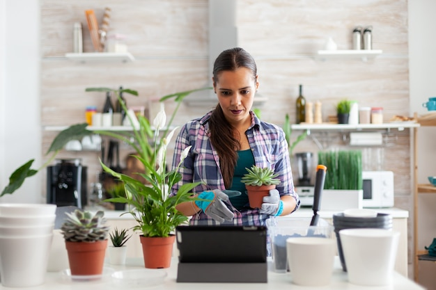 Handschoenen dragen om te tuinieren tijdens het gebruik van een tablet-pc in de keuken thuis en bloemen op tafel