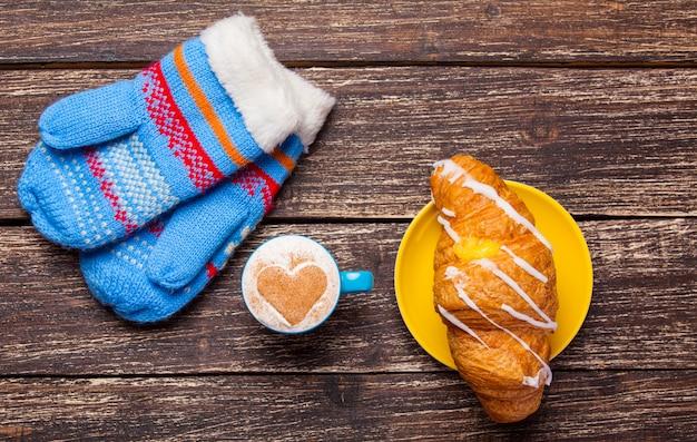 Handschoenen en een kopje koffie op houten tafel.